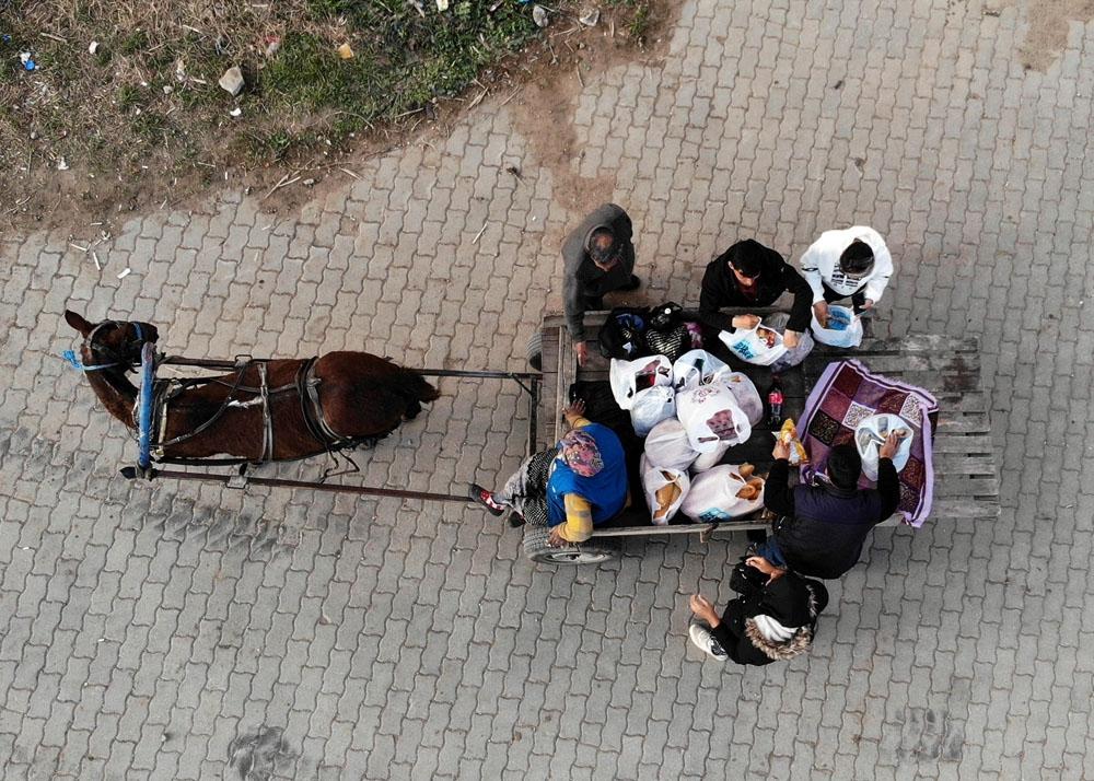 Göçmenlerin at arabasıyla alışveriş yolculuğu